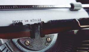 """The words, """"Never Be Afraid"""" typed on a typewriter in black ink."""