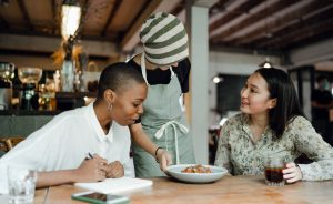 Two women sample a dish of food brought by a server. One is looking at the food, the other smiling at the server.
