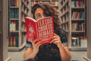 "woman reading a book looking at the camera over the top of the book. the cover of the book reads, ""text, os cures, demos para serum lidos."""