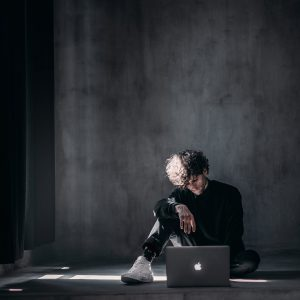 Young man sitting on a concrete floor using a laptop. natural light comes in from a window on the left.
